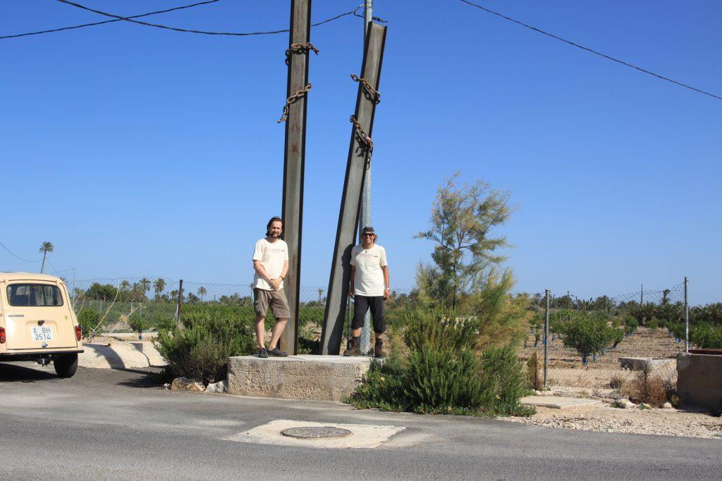 dos senderistas sobre monumento en el camino