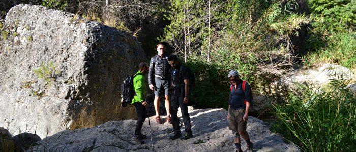 Senderistas sobre roca junto al río